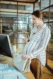 Gravid kvinna med läsande anvisning för trevlig hårbulle till vitaminer royaltyfria bilder