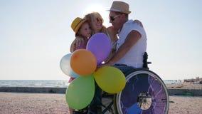 Gravid kvinna med lilla flickan och den handikappade personen på havet, föräldrar med barnet på öppen luft, mamma och dotter lager videofilmer