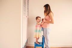 Gravid kvinna med litet barndottern som har gyckel hemma Fotografering för Bildbyråer