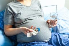 Gravid kvinna med magen och rymma i hennes händer och piller och exponeringsglas av vatten Behandling av gravida kvinnor fotografering för bildbyråer
