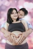 Gravid kvinna med make- och hjärtasymbol Arkivbild