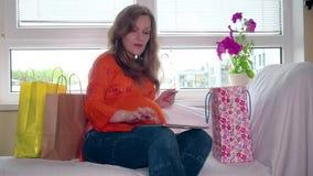 Gravid kvinna med minnestavladatoren och kreditkortar som direktanslutet shoppar arkivfilmer