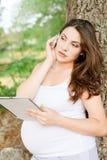 Gravid kvinna med minnestavlaPC Royaltyfria Foton