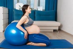 Gravid kvinna med passformbollen royaltyfri bild