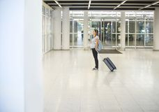 Gravid kvinna med resväskan på flygplatsen eller stationen royaltyfri fotografi