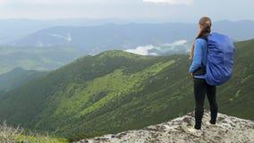Gravid kvinna med ryggsäckanseende på berget stock video
