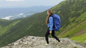 Gravid kvinna med ryggsäcken i bergen stock video