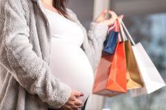 Gravid kvinna med shoppingp?sar som trycker p? hennes buk arkivfoton
