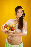 Gravid kvinna med skörden för vide- korg Royaltyfri Bild