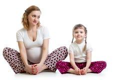 Gravid kvinna med ungen som gör yogaövningar royaltyfri foto