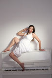 Gravid kvinna nära vitpiano royaltyfri bild