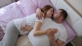 Gravid kvinna och en man i vitt t-skjortor ligga arkivfilmer