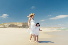 Gravid kvinna och hennes dotter på stranden fotografering för bildbyråer