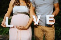 gravid kvinna och hennes make som rymmer bokstäverna för förälskelse i deras händer med royaltyfri bild
