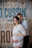 Gravid kvinna och man som tillsammans poserar i studion Royaltyfria Foton