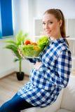 Gravid kvinna som äter grönsaker Arkivfoto