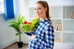 Gravid kvinna som äter grönsaker Royaltyfria Bilder