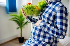 Gravid kvinna som äter grönsaker Royaltyfri Fotografi