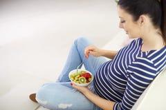 Gravid kvinna som äter ny sund fruktsallad arkivfoton