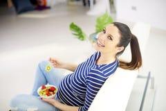 Gravid kvinna som äter ny sund fruktsallad arkivbild