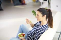 Gravid kvinna som äter ny sund fruktsallad arkivbilder