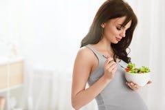 Gravid kvinna som äter sund sallad Arkivfoton