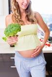 Gravid kvinna som äter sunda visninggrönsaker Fotografering för Bildbyråer