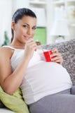 Gravid kvinna som äter yoghurt Arkivfoto
