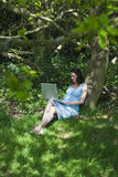 Gravid kvinna som använder bärbara datorn i trän Arkivfoton