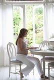 Gravid kvinna som använder bärbara datorn i vardagsrum Royaltyfri Foto