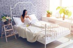 Gravid kvinna som använder bärbara datorn och har frukosten i säng Arkivbild