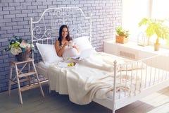 Gravid kvinna som använder bärbara datorn och har frukosten i sovrummet Royaltyfri Bild