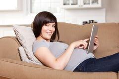 Gravid kvinna som använder den Digital minnestavlan Arkivfoto