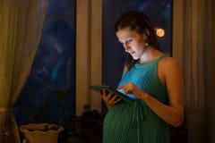 Gravid kvinna som använder minnestavlan i aftonen Arkivbilder