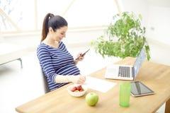 Gravid kvinna som använder mobiltelefonen och bärbara datorn royaltyfria foton
