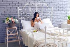 Gravid kvinna som arbetar i säng och har frukosten Royaltyfri Bild
