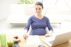 Gravid kvinna som arbetar på bärbara datorn royaltyfri foto