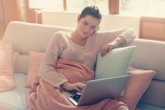 Gravid kvinna som arbetar på en soffa arkivbild