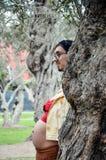 Gravid kvinna som bakifrån döljer hennes framsida ett träd och en pojkvän som av tar hennes framsida, roligt foto av gravid arkivbilder