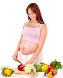 Gravid kvinna som förbereder mat. Arkivbild