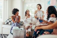 Gravid kvinna som firar hennes baby shower med vänner Royaltyfri Fotografi