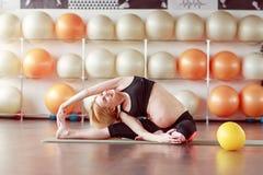 Gravid kvinna som gör övningar i idrottshallgrupp Arkivfoton