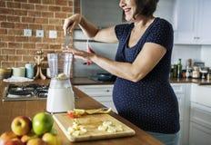 Gravid kvinna som gör den sunda smoothien Fotografering för Bildbyråer