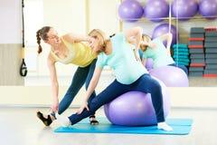 Gravid kvinna som gör konditionbollövning med lagledaren Arkivfoto