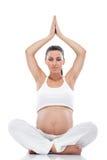 Gravid kvinna som gör yoga arkivfoton