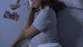Gravid kvinna som gråter i säng, sönderrivna det närliggande familjfotoet, svek och skilsmässa stock video
