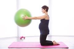 Gravid kvinna som håller i form Arkivfoto