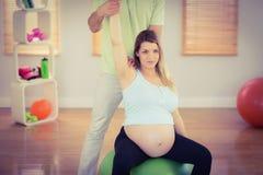Gravid kvinna som har avslappnande massage, medan sitta på övningsboll royaltyfria foton