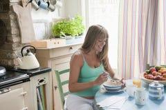 Gravid kvinna som har frukosten royaltyfri bild