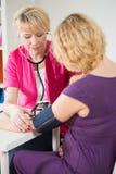Gravid kvinna som har tryck att mätas Royaltyfri Foto